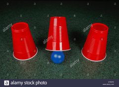 shell-game-three-red-cups-and-a-blue-ball-on-a-green-table-arranged-E7E8TE.jpg